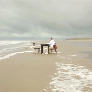 Man sits at table on beach