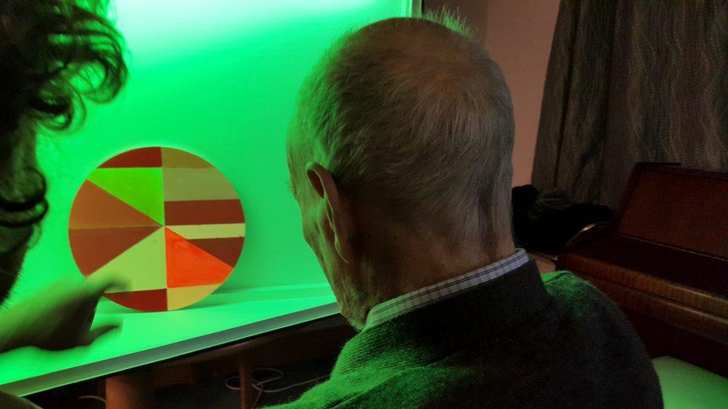 Older person looks at light artwork