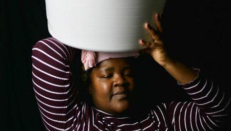 Art photograph of woman carrying bucket