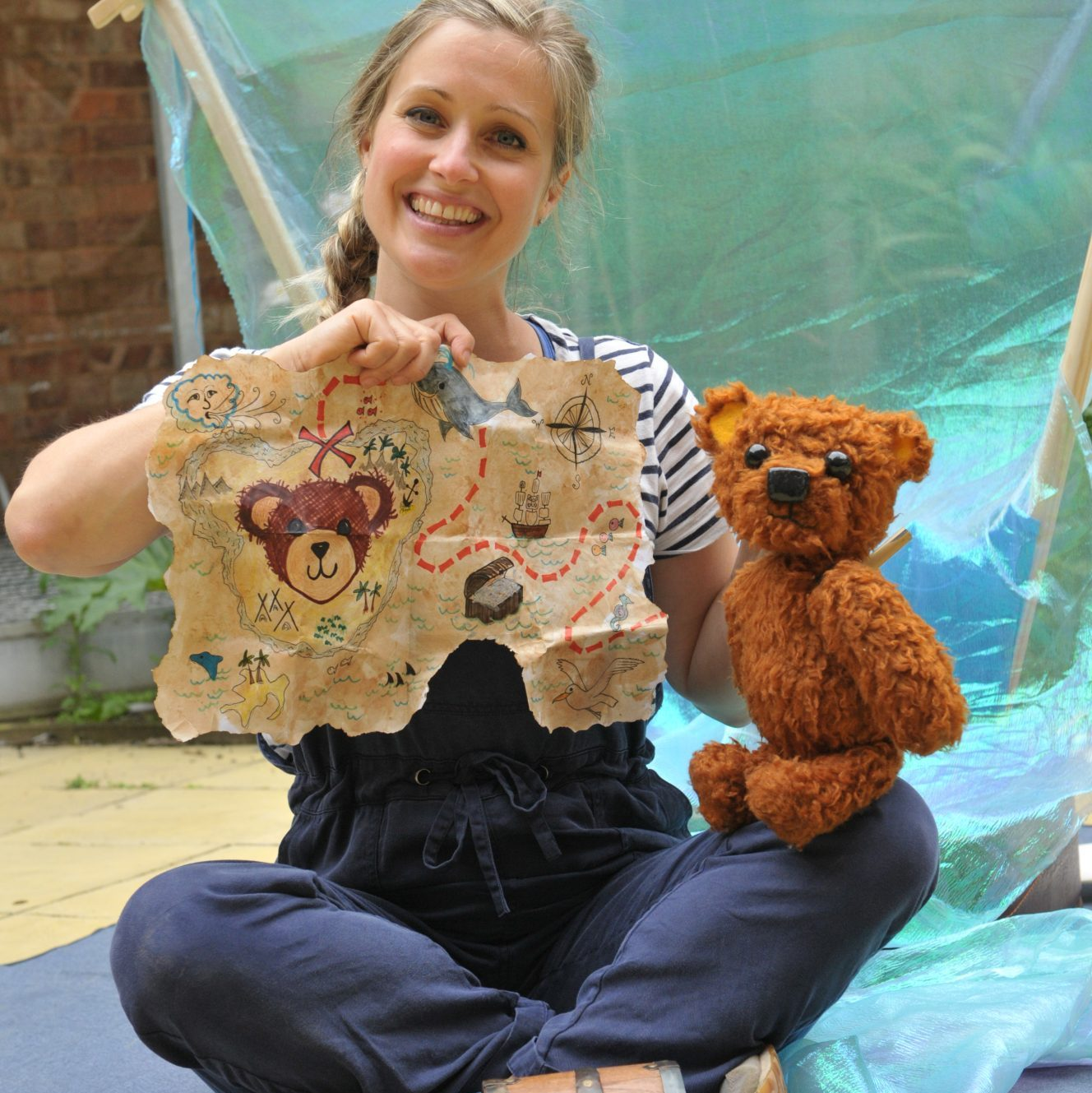 Performer holding Teddy Bear Puppet and Treasure Map