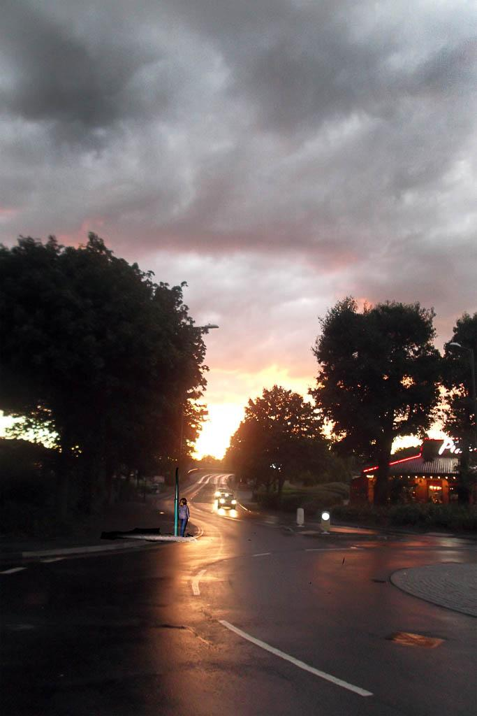 Light over an empty street. One person stands at a lamppost. Two car a driving towards the viewer.