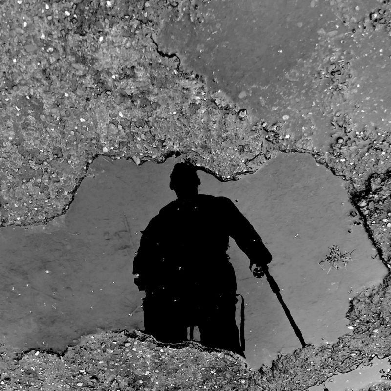 Photographer Tony Fisher reflected in a puddle