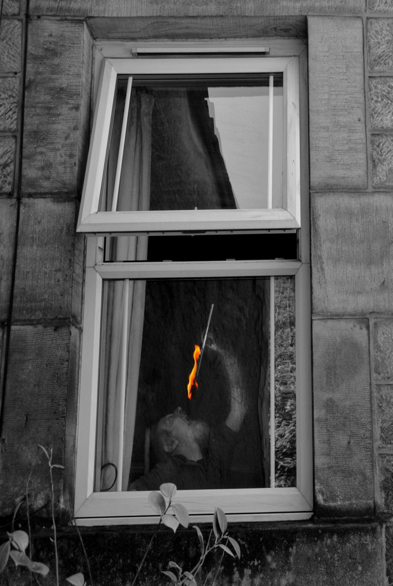 Black & White Photograph. Fire-eater performs behind a window.