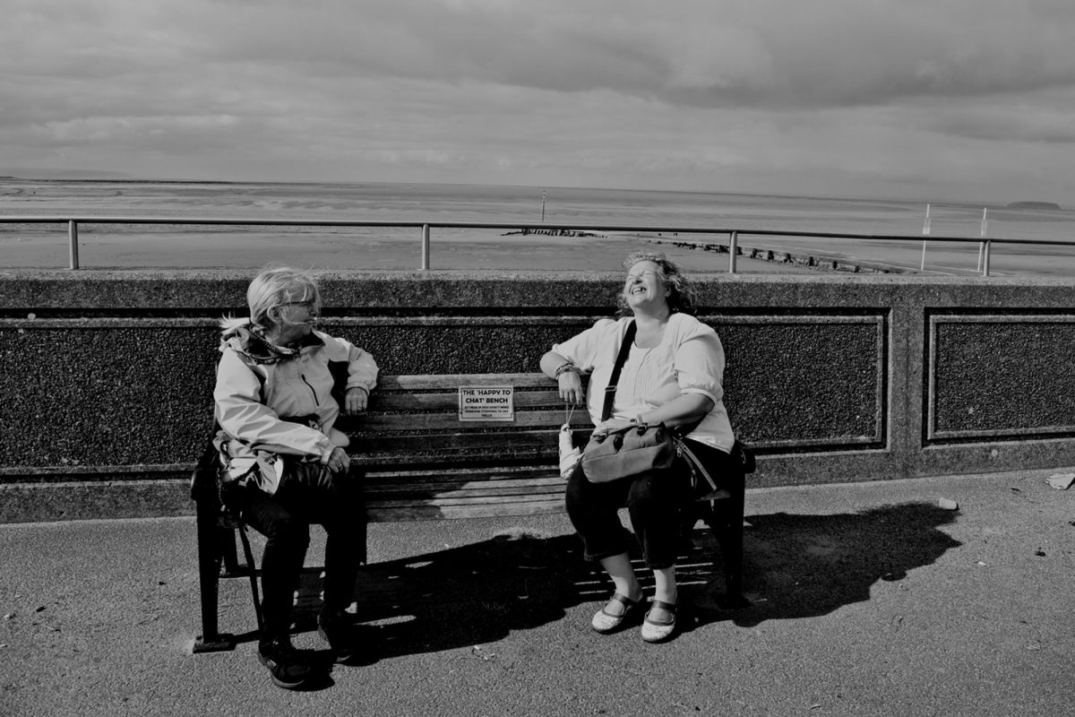 Black & White Photograph. Founders of the 'Happy to Chat Bench' in Burnham-On-Sea sitting on the bench.