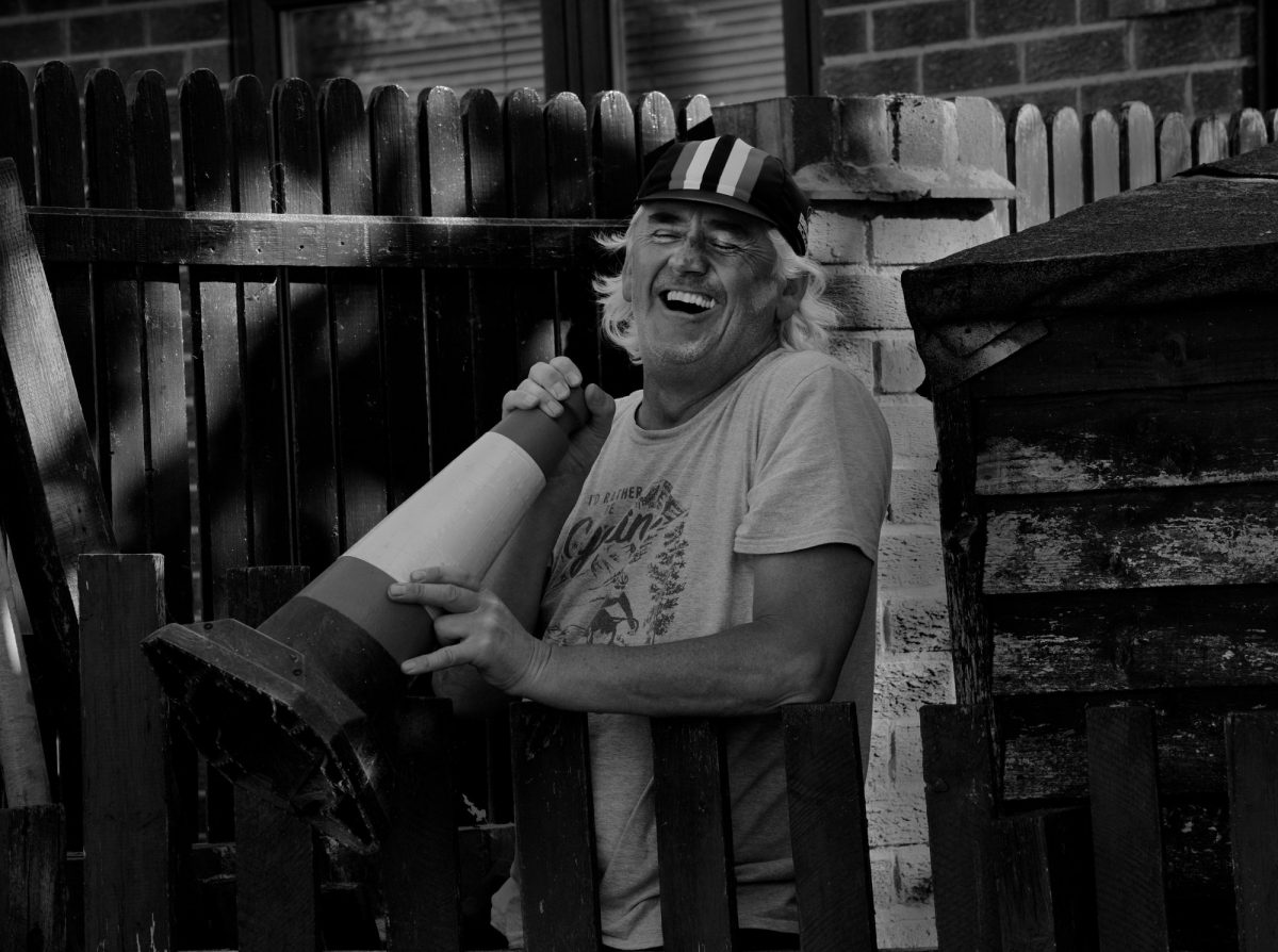 Black & White Photograph. Belper man laughs whilst holding a traffic cone.