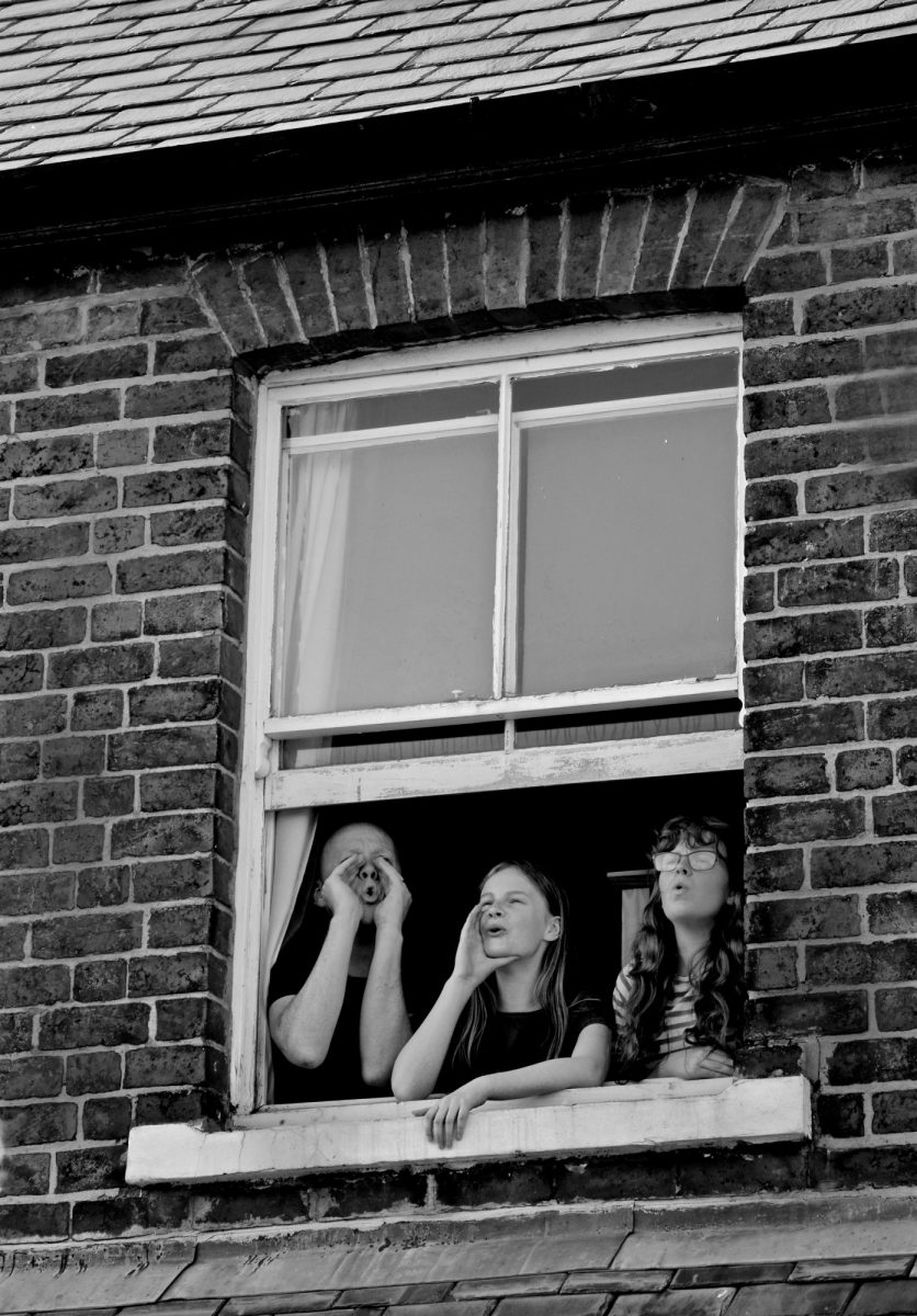 Black & White Photograph. Family lean out of upper floor window to make mooing sound.