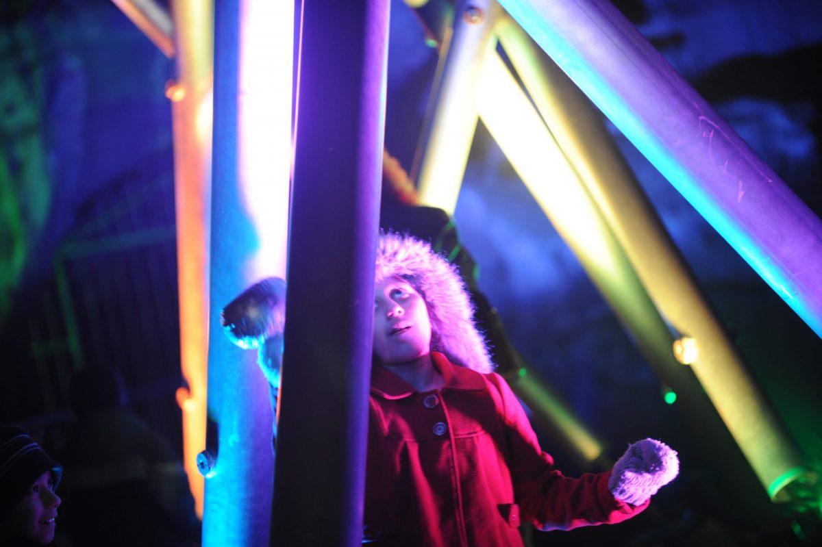 Child playing illuminated chime instruments
