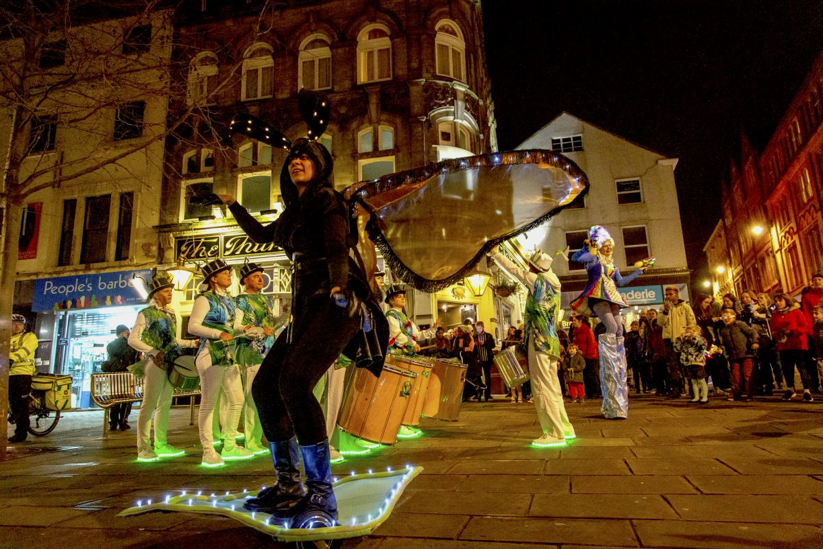 Carnival performer dressed as bee at night
