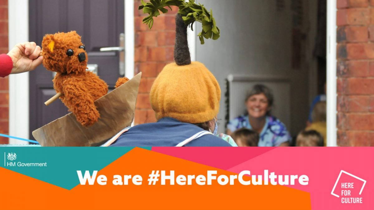 Image of doorstep puppet show with banner reading 'We are #HearForCulture'