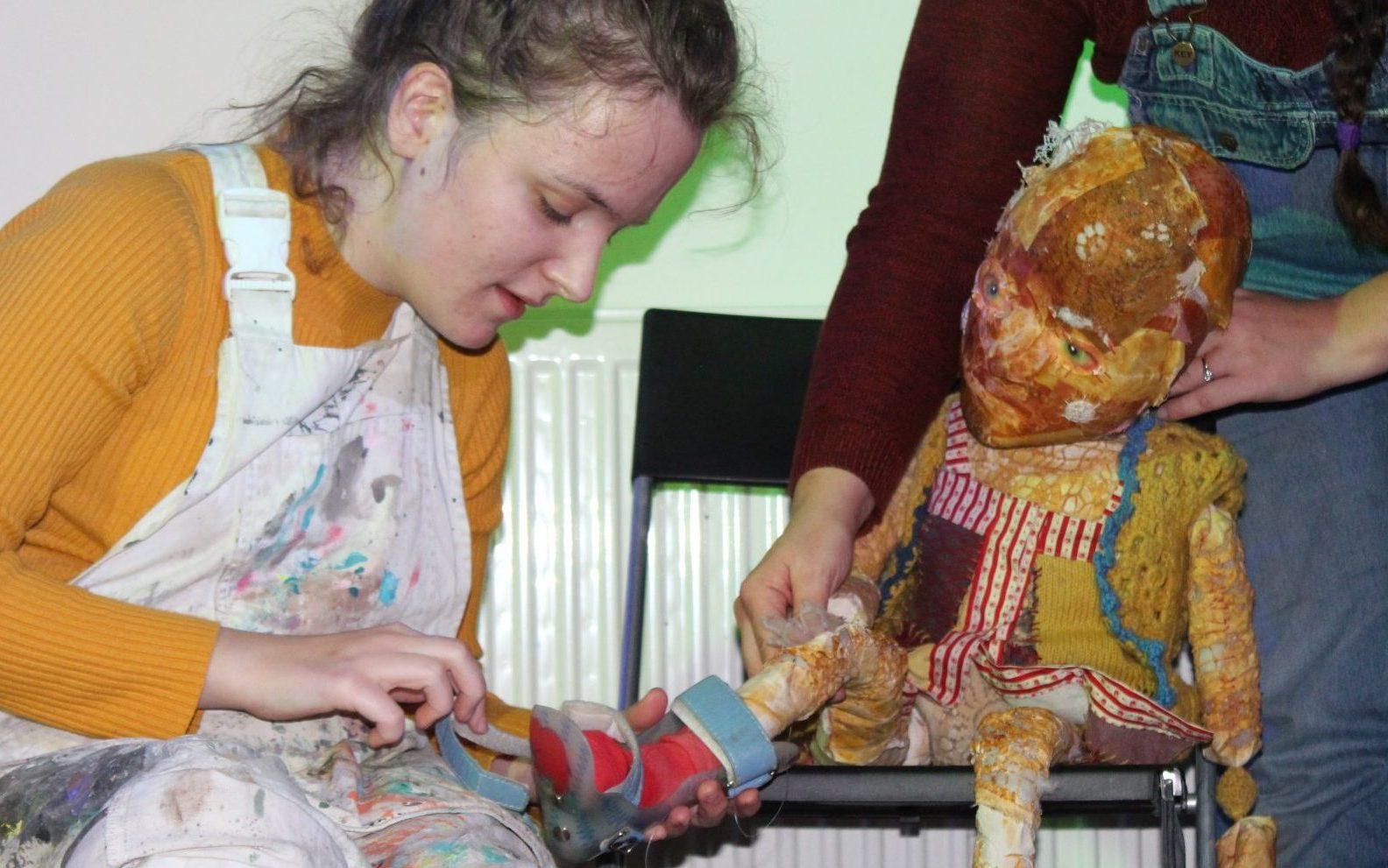 Nikki placing orthotics on a patchwork puppet