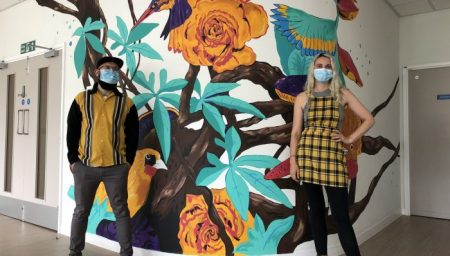 Alastair Flindall, Megan Russell standing in front of a mural featuring birds and flowers