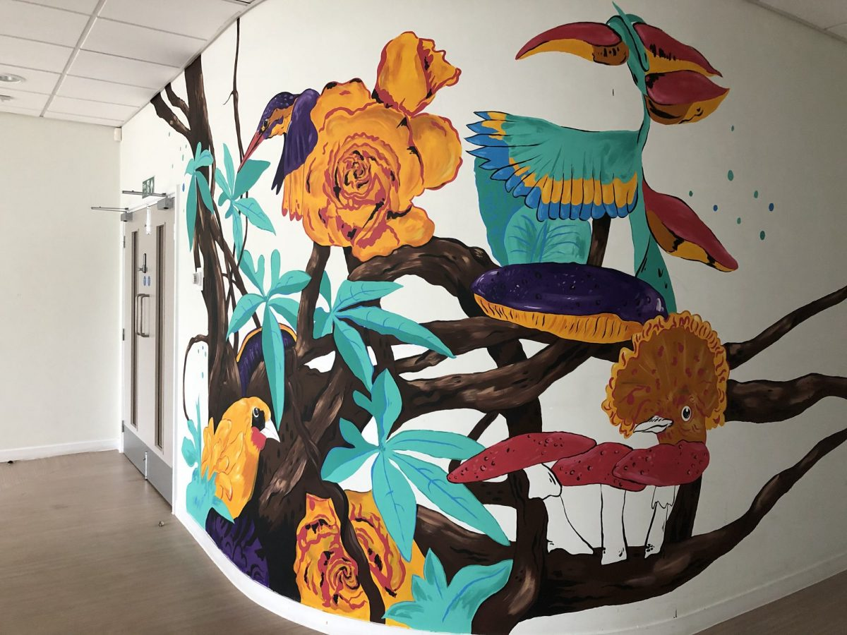 A mural featuring birds, flowers branches and mushrooms