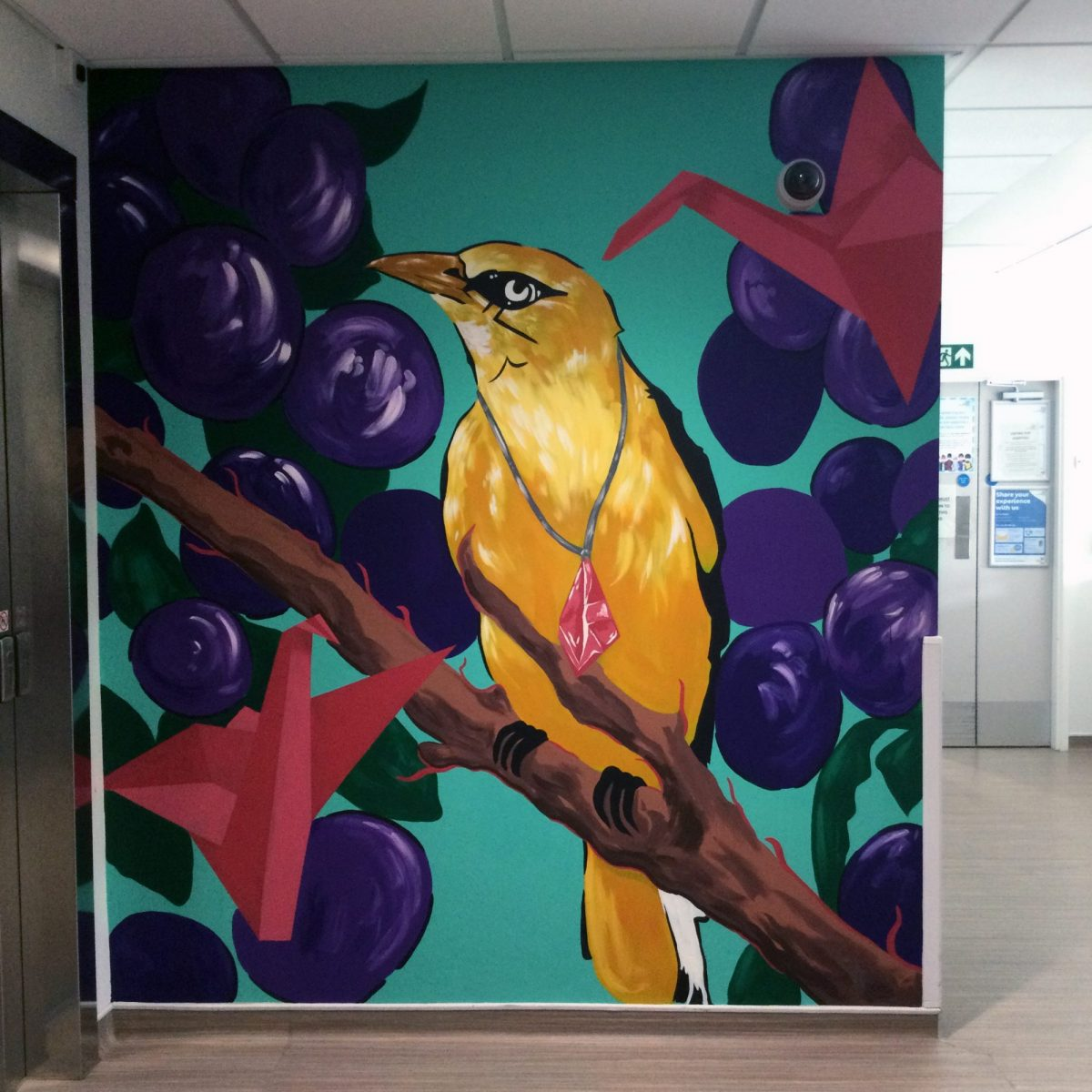 A mural featuring a bird sat on a branch, as well as origami birds, painted in the Wolfson Cystic Fibrosis Centre