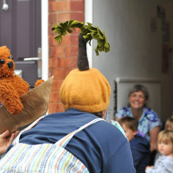 Teddy puppet in boat next to performer with palm tree hat