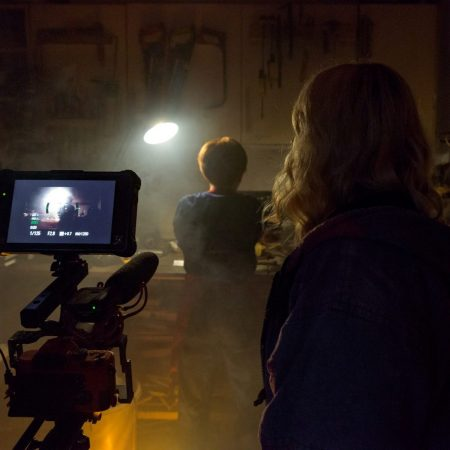 Back of young womans head as she films in a dark shed