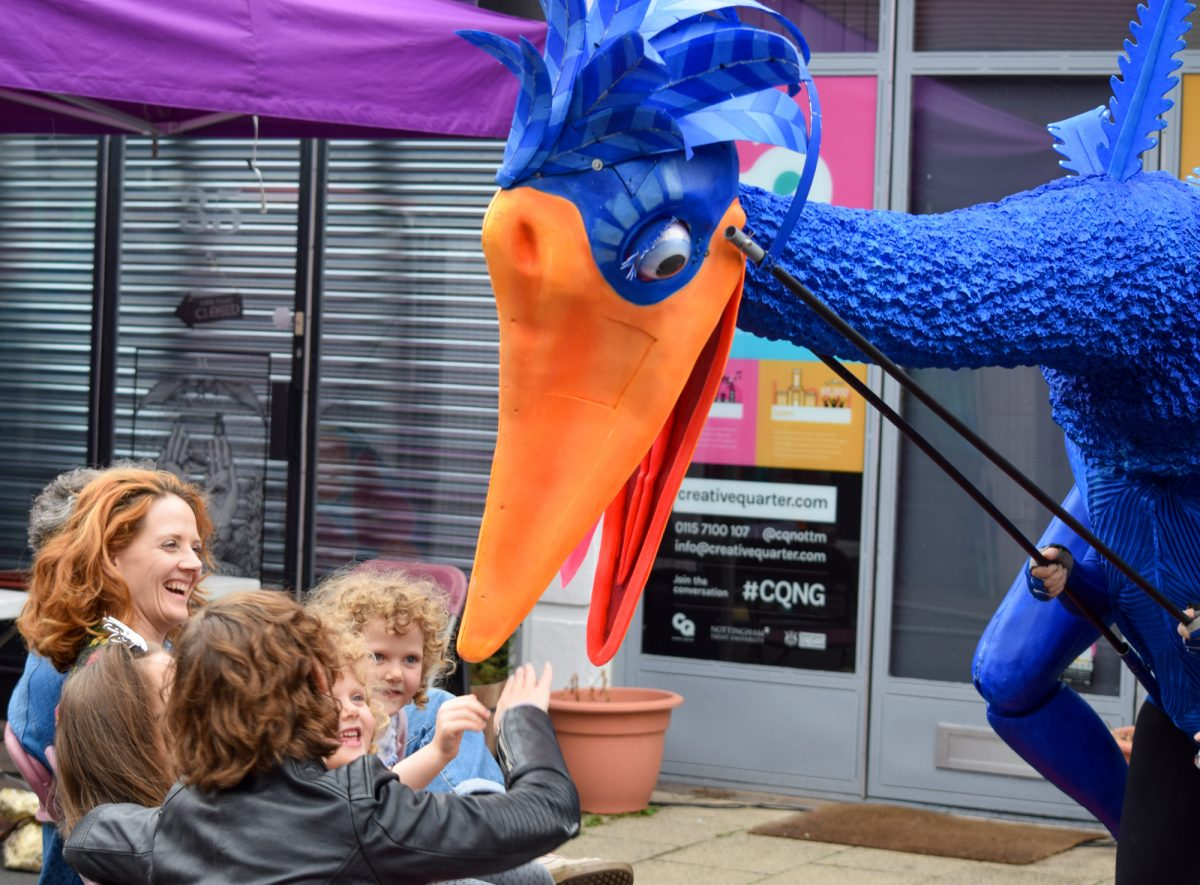 Giant blue bird puppet appears to bite audience members at an outdoor theatre performance