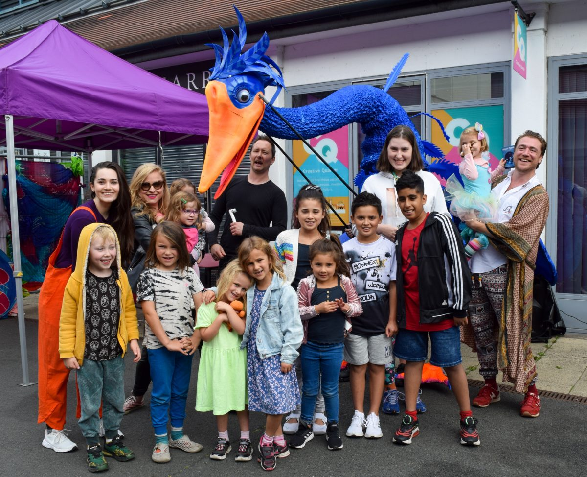 A group photo featuing JINGAH cast member, a giant blue bird puppets and members of the show's audience