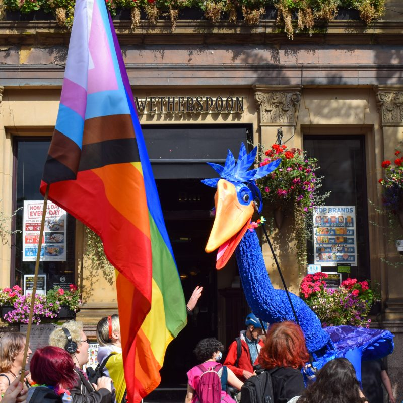 Giant blue bird puppet out side Wetherspoons at Nottingham Pride. The images also shows a crowd carrying a pride flag.