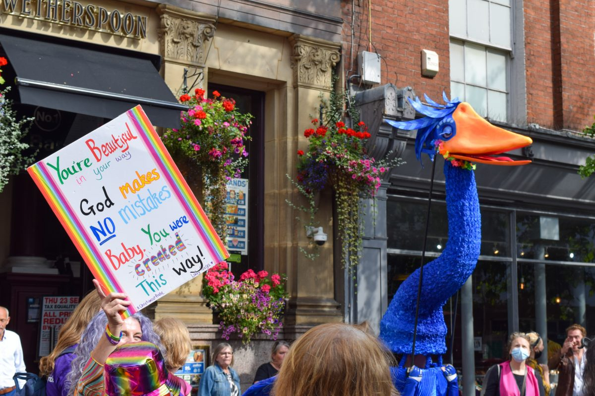 Giant blue bird puppet near a protest plaquard at Nottingham Pride