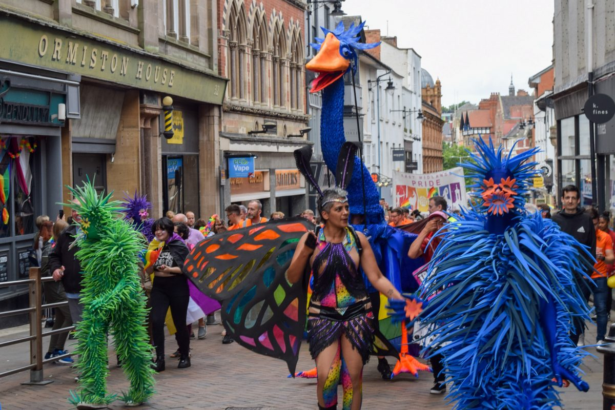Giant blue bird puppet with carnival performers in the Nottingham pride march